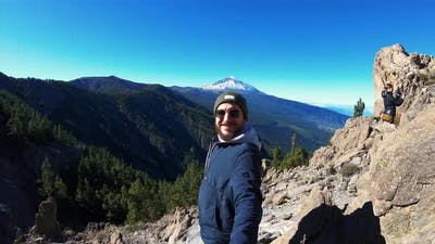 Man in Sunglasses with Beard Climbed to Top of Mountain