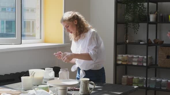 Thumbnail for Female Potter Glazing Raw Unburned Ceramic Cup Using Brush. Earthenware Mug Putting Colorant on