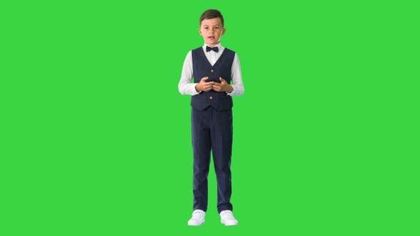 Kleiner Junge in Fliege und Weste, der auf einem Greenscreen-Chroma-Key mit der Kamera spricht