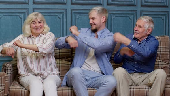 Happy Generation Family of Senior Grandparents with Adult Son Listening to Music Dancing at Home