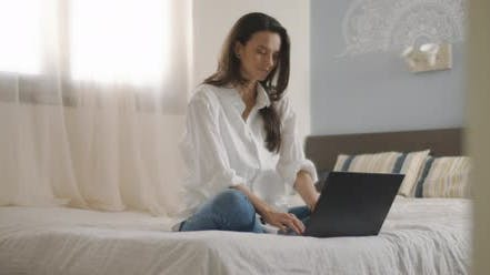 Thumbnail for A young woman smiling while working on her computer from home.
