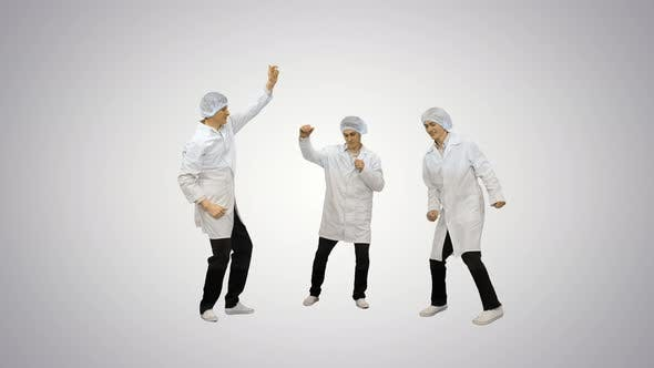 Three Male Doctors in White Robes and Protective Caps Doing Funny Celebration Dance on Gradient