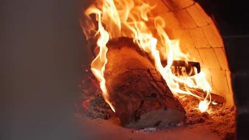 Nahaufnahme mit einem Schieber wie in einem Pizzaofen brennt frisch frisch geworfenes Brennholz einfach fein