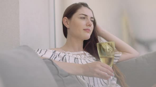Thumbnail for Young adult relaxing with wine at home
