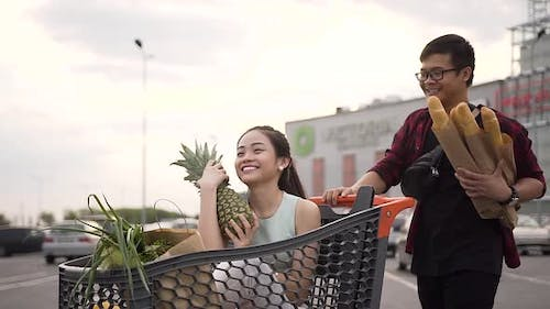 Likable Young Asian Woman Sitting in the Shopping Trolley with Paper Bags