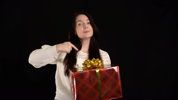 Junge Frau mit einer Geschenkbox auf schwarzem Hintergrund. Geschenkbox mit weißem Band für ein glückliches neues Jahr