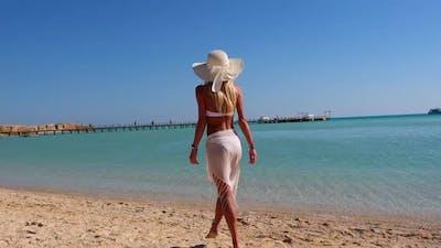 Young Fashion Woman Wearing Pareo Walking on the Beach