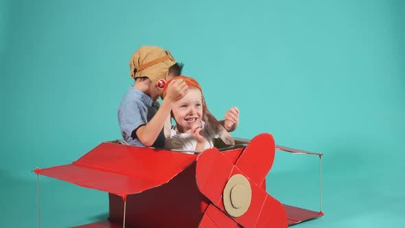 Cute Dreamer Boys Flying in Cardboard Airplane