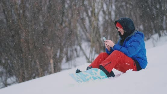 Cover Image for A Male Snowboarder Sitting on the Snow Takes Photos on the Phone of a Beautiful Resort Landscape