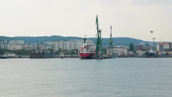 Thumbnail for Industrial zone of seaside city with cranes and cargo ships, view from sea