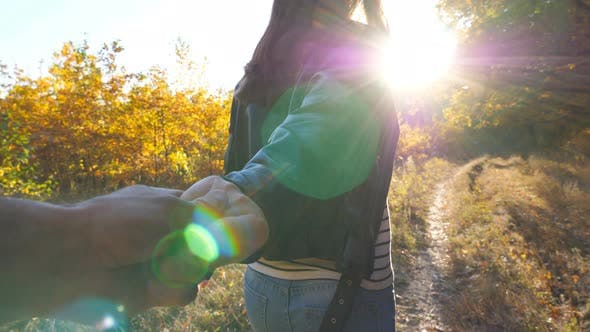 Thumbnail for Young Woman Holds Male Hand and Jogs Along Path Near Woodland. Follow Me Shot of Happy Girl Leads