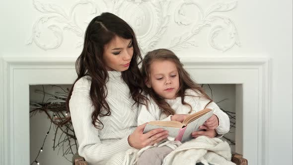 Thumbnail for Young Mother and Her Little Daughter Reading a Christmas Tale