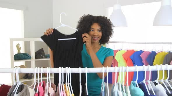 African American woman trying on black dress in boutique