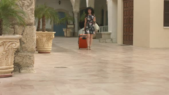 Beautiful Female Arrives in Exotic City on Vacation, Carrying Luggage to Hotel