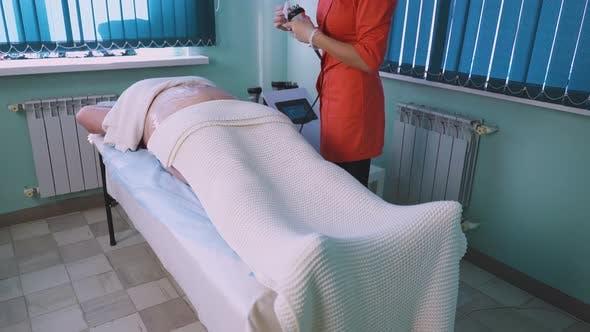 Specialist Prepares Massaging Instrument for Plussize Woman