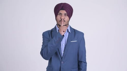 Bearded Indian Sikh Businessman with Finger on Lips