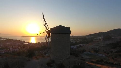 Old Traditional Historic Stone Windmill by the Sea at the Sunset