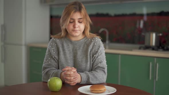 Thumbnail for Portrait Young Chubby Girl Thinks That She Should Eat a Tasty Hamburger or a Juicy Green Apple