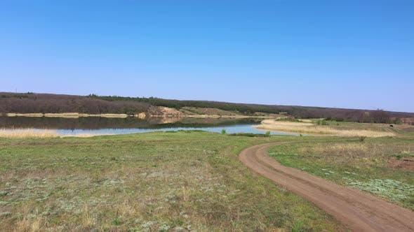 Country road near the lake. Rural scene in spring