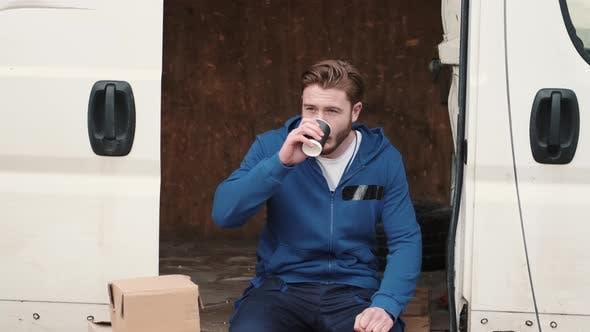 Young Man Drinking Tea Or Coffee Sitting In Van