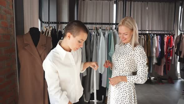 Clothes Designer and Potential Client in Workplace Discuss Suitable Sizes for Clothing