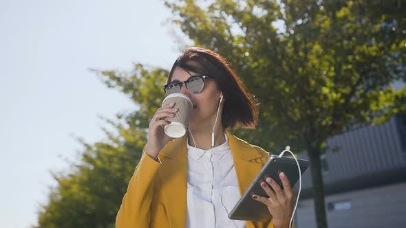 Thumbnail for caucasian young business woman using tablet computer while stands near office centre