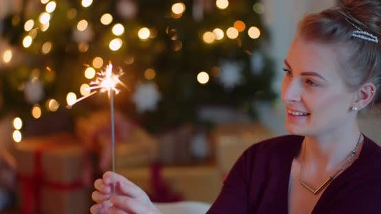 Thumbnail for Blond Woman Holding And Looking At Sparkler