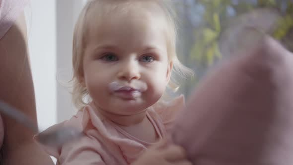 Cover Image for Close-up Face of Caucasian Little Girl Eating Baby Food