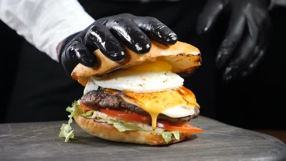 Thumbnail for Male Chef Hand Pressing Juicy Burger Dripping Sauce and Yolk in Slow Motion. American Burger