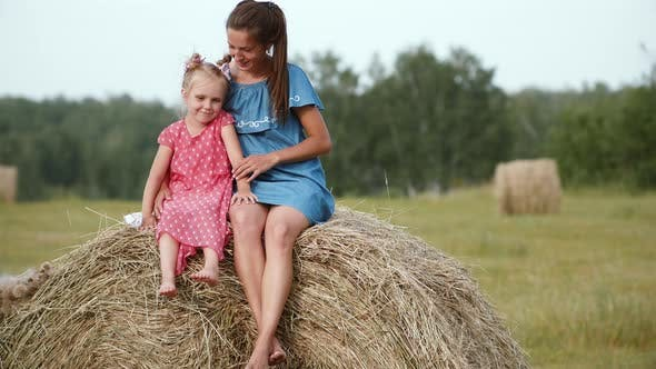 Thumbnail for Mother with daugter sitting on haystack