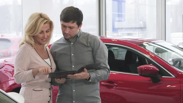 Thumbnail for Mature Couple Reading Booklet at the Car Dealership Buying a New Auto