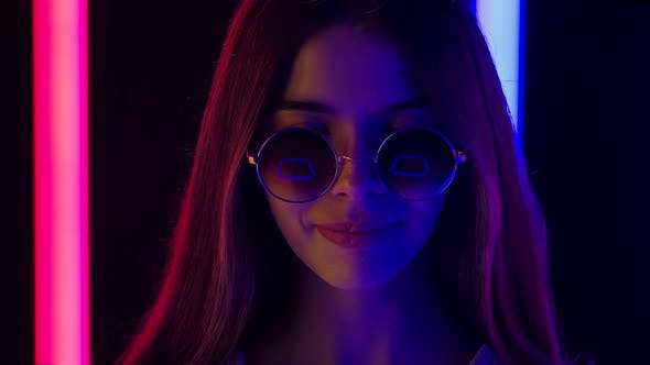 Portrait of a Pretty Young Beautiful Woman in Stylish Round Sunglasses Looking at the Camera and