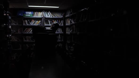 Fluorescent Tubes illuminating an Empty Room with many Books.