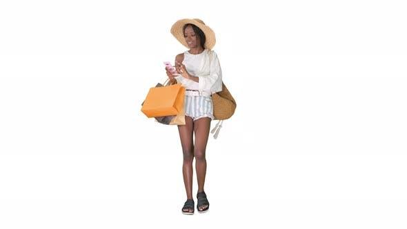 Glückliche Afroamerikanerin mit Hut, die ein Telefon auf weißem Hintergrund läuft