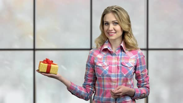 Pretty Woman Pointing at Gift Box with Finger