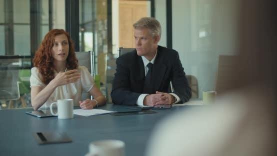 Thumbnail for Mittlere Aufnahme von zwei Personen bei einem Geschäftstreffen mit ihren Kollegen. Zeitlupe