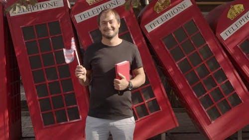 Der Mann hält britische Flagge und Buch, Bildung im Ausland, Sprache lernen.