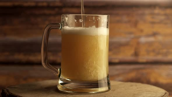 Thumbnail for Beer Is Poured Into a Beer Glass with a Handle, a Lot of Bubbles and Foam That Flows Down the Glass