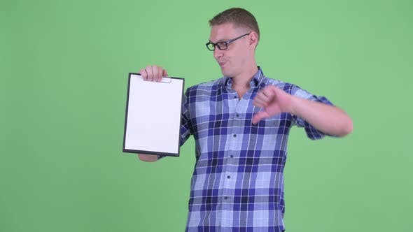 Thumbnail for Stressed Young Hipster Man Showing Clipboard and Giving Thumbs Down