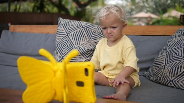 Toddler Child Watching a Cartoon on a Digital Tabled in a Kid Riendly Yellow Butterfly Case