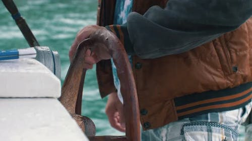 Hands Hold Steering Wheel of the Boat