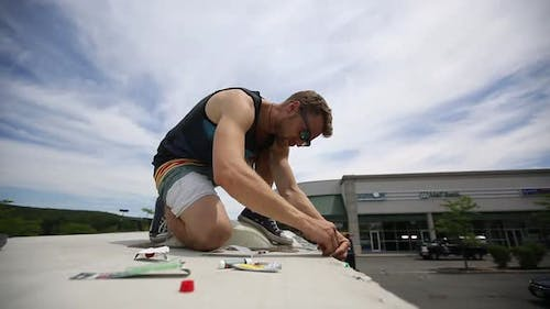 Young Man is Working on Top of a Trailer Van Patching the Roof USA
