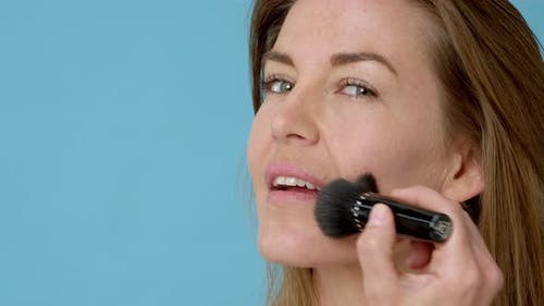 Lady with Fair Skin Complexion Brushing Her Cheeks