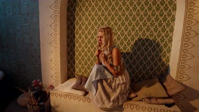 a Blonde with Long Hair is Sitting in a Niche on Pillows and is Sad