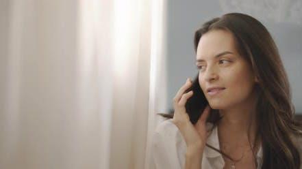 Thumbnail for Nahaufnahme einer Frau im Gespräch mit jemandem am Telefon, in der Nähe des Fensters