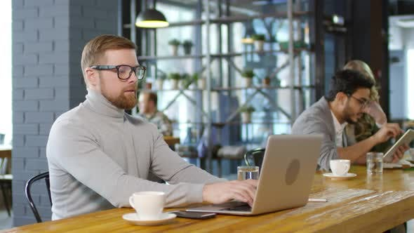 Thumbnail for Caucasian Businessman Working on Laptop and Drinking Coffee in Cafe