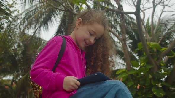 Cute Little Girl Child Using a Digital Tablet Technology Device Telephone or Laptop