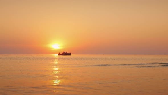 Thumbnail for A Beautiful Sunset Over the Calm Sea, in the Distance a Lonely Boat Sails