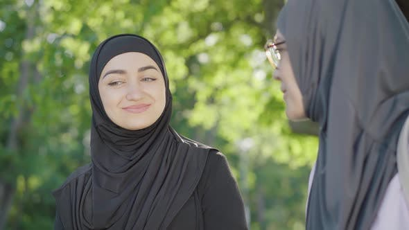 Thumbnail for Close-up Portrait of Beautiful Young Muslim Woman in Black Hijab Talking with Blurred Friend and