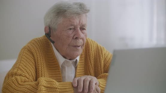 Thumbnail for Old Woman Talk with Her Granddaughter on Video Call Using a laptop.Video Conference with a Doctor